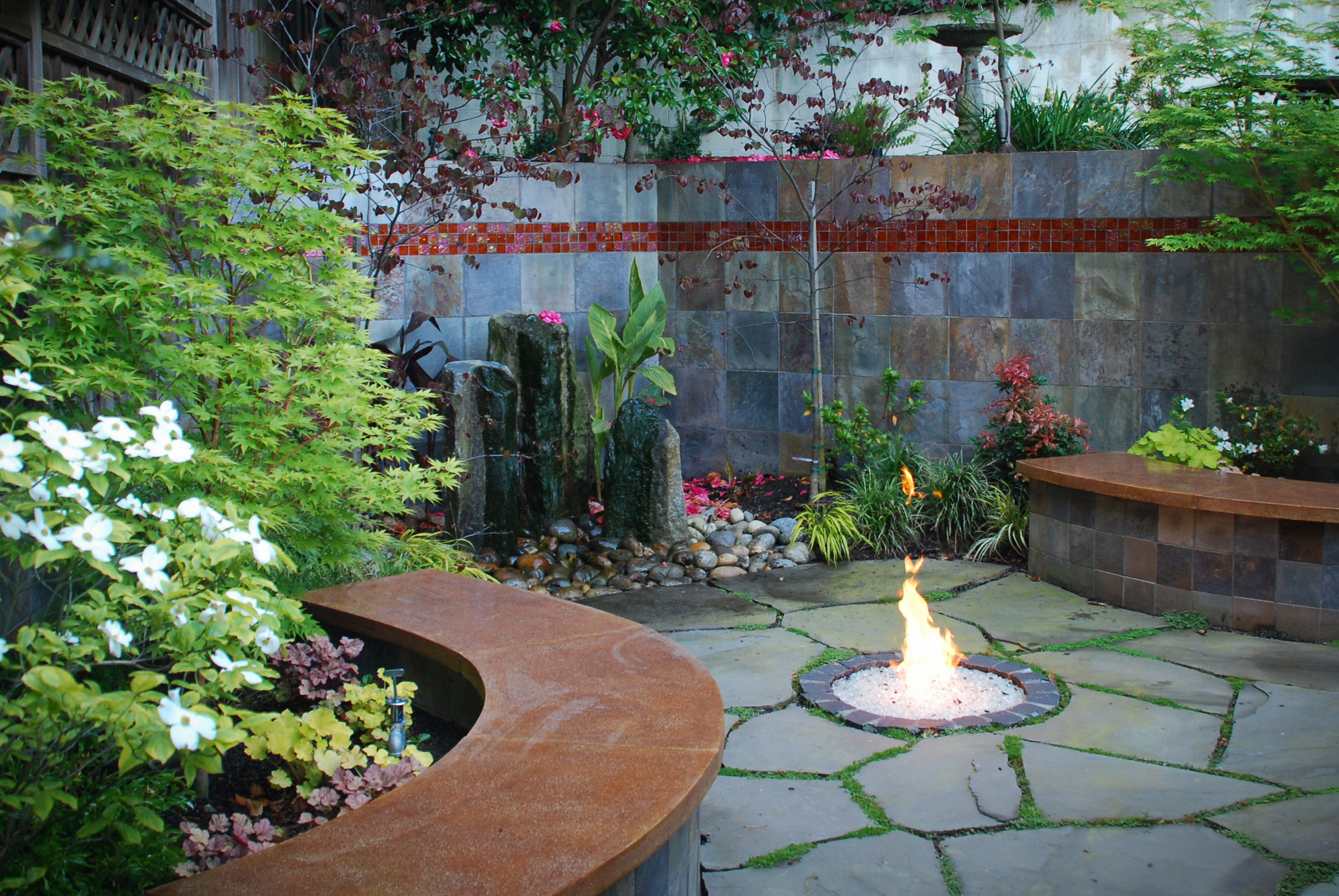 photo depicting water bubbler feature and in-ground fire pit